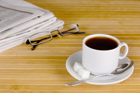 Cup of black coffee on the wooden table with glasses and newspaper aside photo