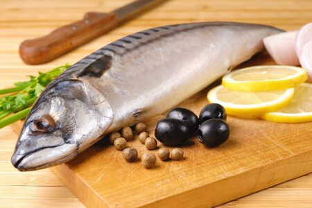 Fresh mackerel with olives, lemon and onions over wooden chopping board Stock Photo - 8681014