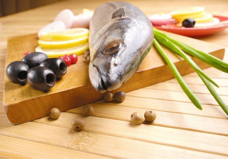 Fresh mackerel with olives and onions over wooden chopping board photo