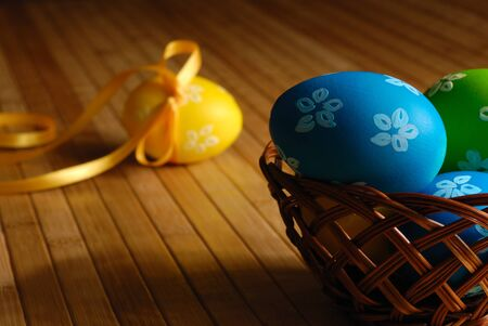 Easter eggs in wicker basket on the wooden table dark photo Stock Photo - 8680900