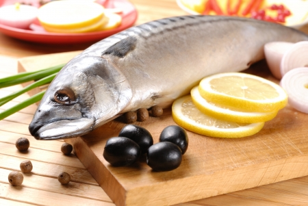 Fresh mackerel with olives, lemons and onions over wooden chopping board