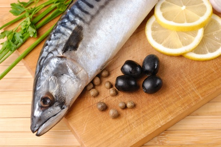 Fresh mackerel with olives, lemons and onions over wooden chopping board photo