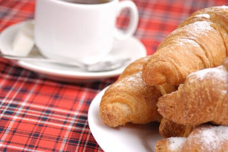 Coffee cup and croissants over checkered tablecloth Stock Photo - 8681057