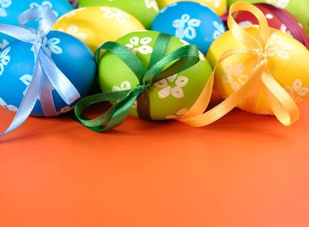 Painted easter eggs with bows over orange background Stock Photo - 8681055