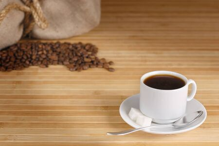 Coffee cup, beans and sack on the wooden table photo
