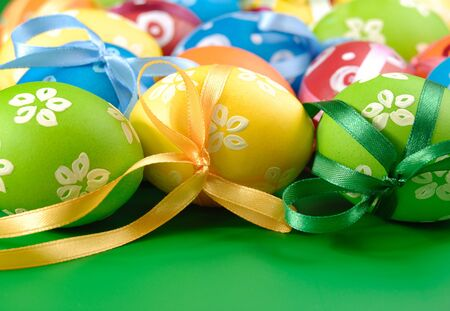 Painted easter eggs with bows over orange background photo
