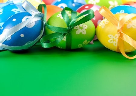 Painted easter eggs with bows over green background photo