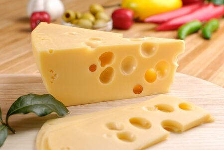 emmental: Emmental cheese with vegetables on the cutting board