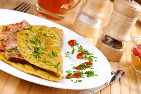 Omelet with bacon served on white plate photo