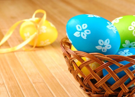 Easter eggs in wicker basket on the wooden table photo