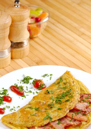 Omelet with bacon served on white plate, spices aside photo