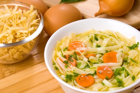 egg noodles: Noodle soup with carrots on the wooden table Stock Photo
