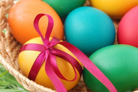 Painted easter eggs in wicker basket photo