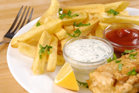 eating fish: White plate with fish and chips, mayo, lemon and ketchup