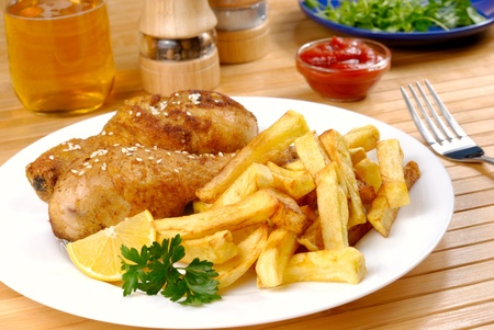 Fried chicken legs with lemon and potato served on the white plate  photo