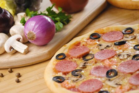 Pepperoni pizza with mushrooms, shrimps and olives photo