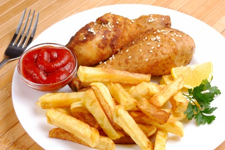 french fries plate: Fried chicken legs with lemon and potato served on the white plate