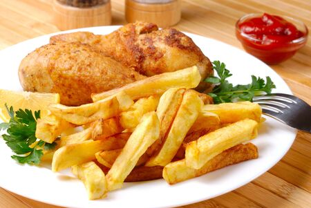 Fried chicken legs with lemon and potato served on the white plate  Stock Photo - 9071737