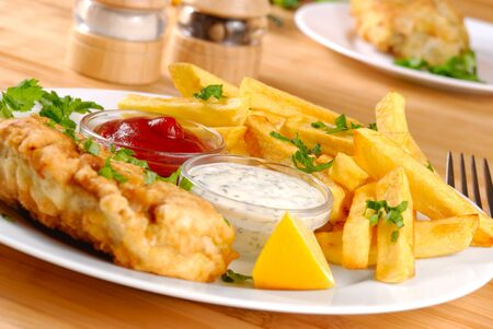 Plato blanco con fish and chips, mayo y salsa de tomate Foto de archivo