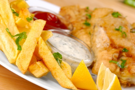 White plate with fish, chips, mayo, ketchup and lemon photo