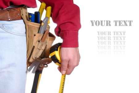 Carpenter in tool belt closeup holds measure tape over white background Stock Photo