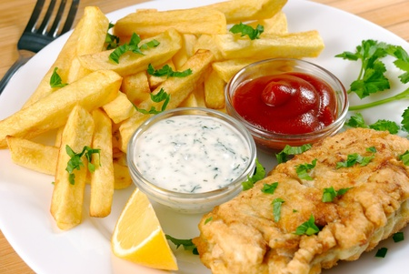 White plate with fish and chips, mayo, lemon and ketchup photo