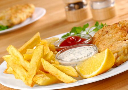 Fish, chips, mayo and ketchup on the white plate Stock Photo