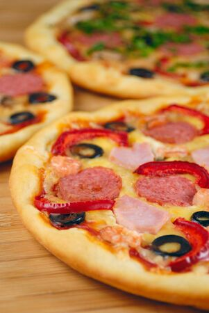 Pepperoni pizzas with mushrooms, peppers and olives on the kitchen table photo