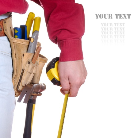 repairman: Carpenter in tool belt closeup holds measure tape over white background Stock Photo