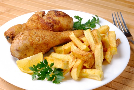 Fried chicken legs and potato chips photo