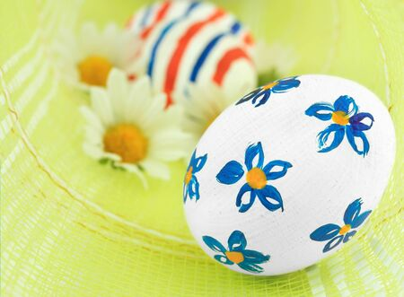 Easter eggs with chamomiles over green background Stock Photo - 9290750