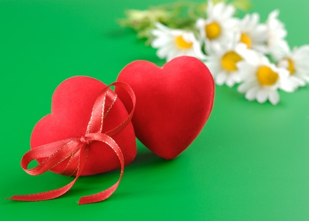 Couple of Red hearts and chamomiles over green background Stock Photo - 9290856