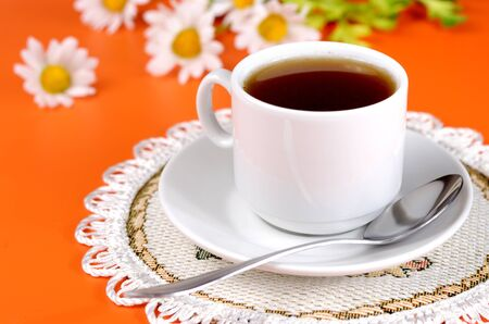 Cup of drink and chamomiles over orange background photo