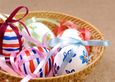 Wicker basket with easter eggs on canvas photo