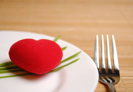 White plate with red heart served with green onion photo