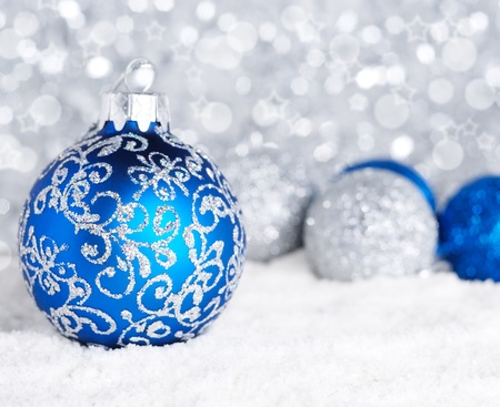 Blue and silver christmas balls on the snow over blurry background, shallow depth of field