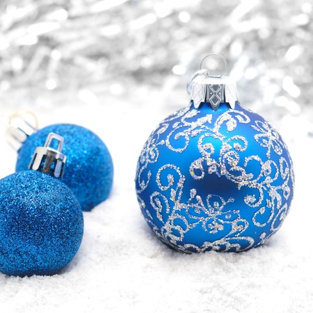 Blue christmas balls on the snow over blurry background, shallow depth of field photo