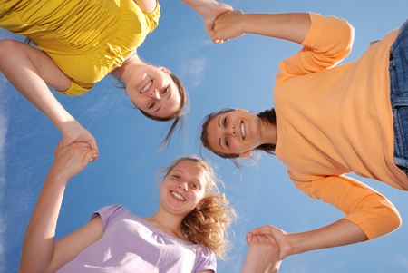 Group of three friends smiling with heads together looking at camera. Low angle view.  Stock Photo - 9287378