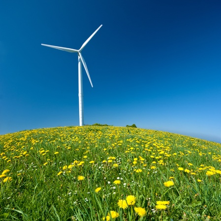 Electricity power wind turbine against blue sky background  photo