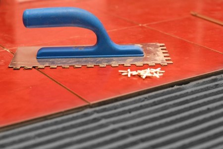 notched: Notched trowel, spacers and prepared setting compound for tile lying Stock Photo