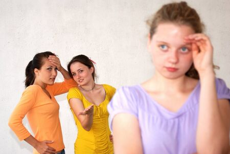 mockery: Girls pointing at their friend. Uniform background