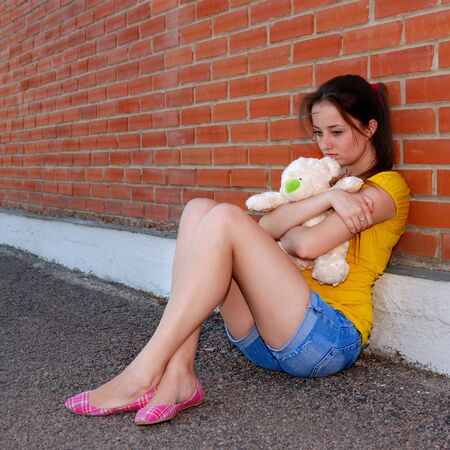 Sad teenager girl with teddy bear sitting near brick wall