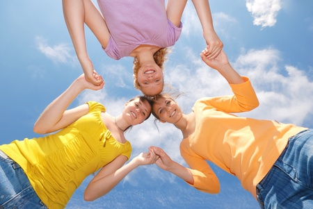 Group of three friends smiling with heads together looking at camera. Low angle view.  photo