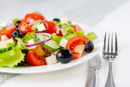 plato de ensalada: Ensalada griega en el detalle de plato blanco dispar�