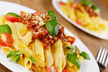 Rigatoni pasta with a tomato beef sauce in the white plate