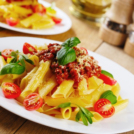 Rigatoni pasta with a tomato beef sauce on the oak table