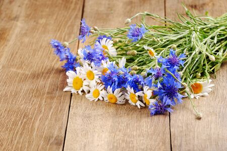 Fresh chamomile and cornflower flowers on the wooden background photo