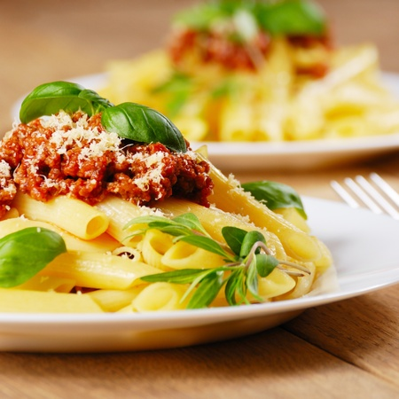 pasta: Rigatoni pasta with a tomato beef sauce on the kitchen table Stock Photo