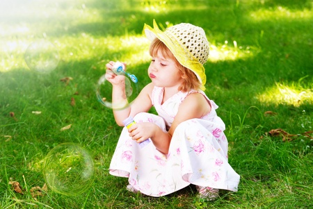 Little beautiful girl blowing soap bubbles  photo