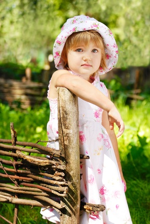 Portrait of a little sad girl standing by fence Stock Photo - 10054615